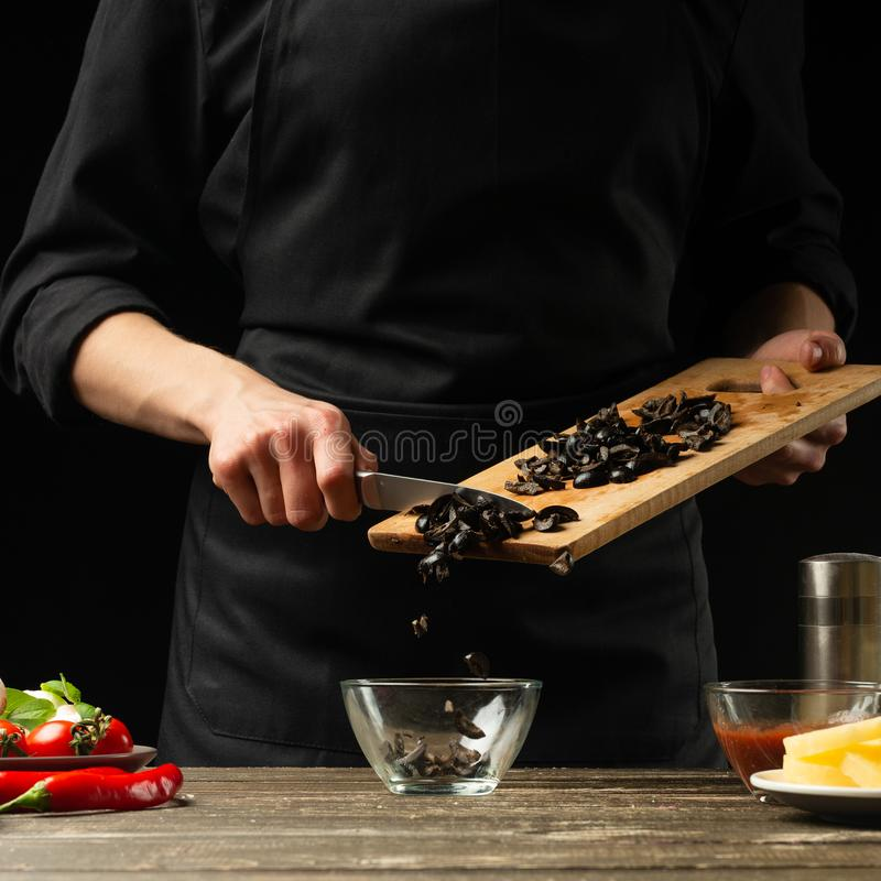 The chef pours olives. Frosting in motion. For cooking pizza, salad. A delicious meal concept. On a black background for design or. Lettering text royalty free stock photo