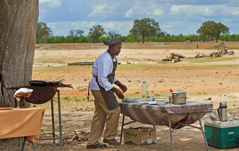 Chef préparant le petit déjeuner dans le buisson pour des invités de safari, parc national de Hwange, 2013 photos stock