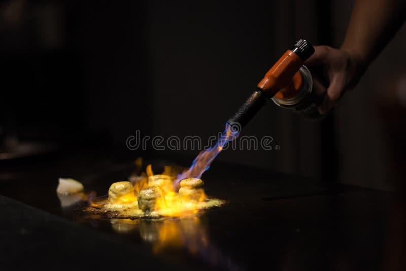 Chef préparant le plat avec la torche de gaz image libre de droits