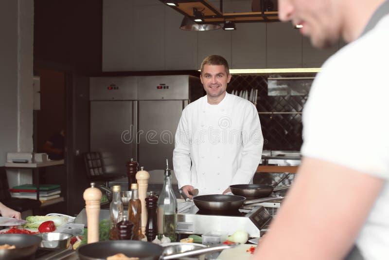 Chef préparant le repas pendant les cours de cuisine dans la cuisine de restaurant image libre de droits