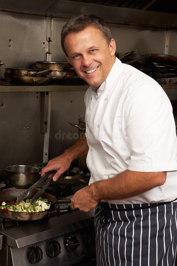 Chef préparant le repas sur le cuiseur dans la cuisine image stock