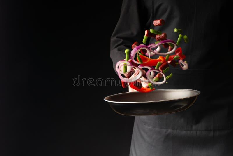 Chef pr?parant des saucisses de pepperoni avec les haricots verts, paprikas doux et anneaux d'oignon rouge, sur un fond noir, un  photo libre de droits