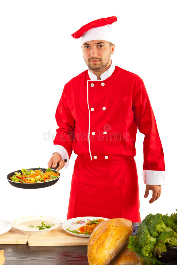Chef prepare food. Chef male prepare vegetables in frying pan in kitchen royalty free stock images