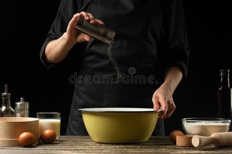 The chef prepares the dough for bread, pizza and sweets. The concept of food. On a black background, freezing in motion. Book of stock photo