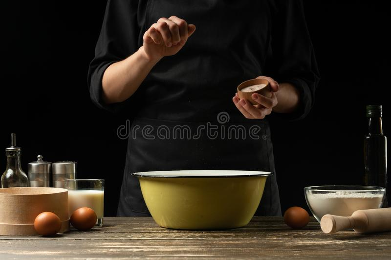 The chef prepares the dough for bread, pizza and sweets. The concept of food. On a black background, freezing in motion. Book of stock image