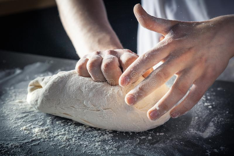 Chef prepares the dough with flour. Hands kneading raw dough Horizontal. Copy space. Gluten free dough for pasta, bakery or pizza. Baker workplace. Chef makes royalty free stock images