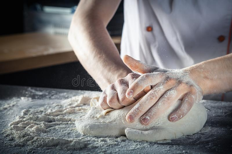 Chef prepares the dough with flour. Hands kneading raw dough Horizontal. Copy space. Gluten free dough for pasta, bakery or pizza. Baker workplace. Chef makes royalty free stock photos