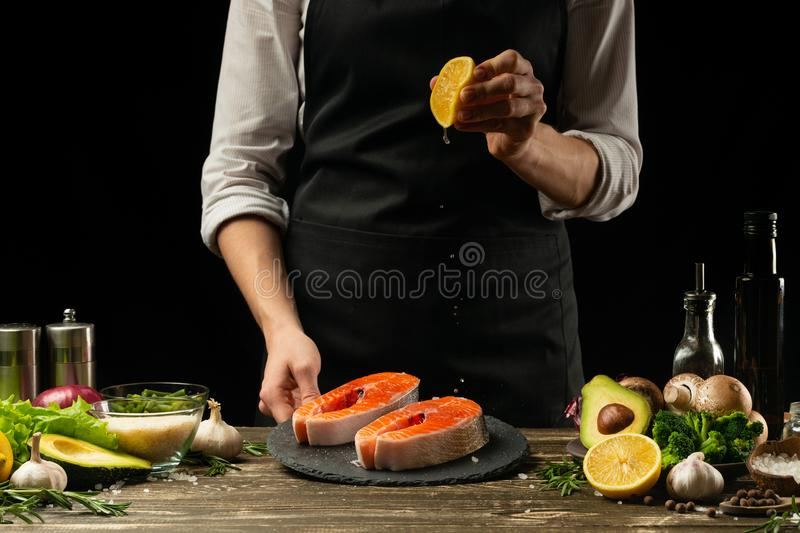 The chef prepares fresh fish salmon, trout, lemon watering with vegetables. Horizontal photo. Concept cooking healthy and vegan royalty free stock photography