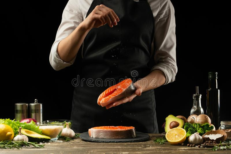 The chef prepares fresh salmon fish, Crumbu trout, sprinkles sea salt with ingredients. Preparing fish food. Salmon steak. Cooking royalty free stock photos