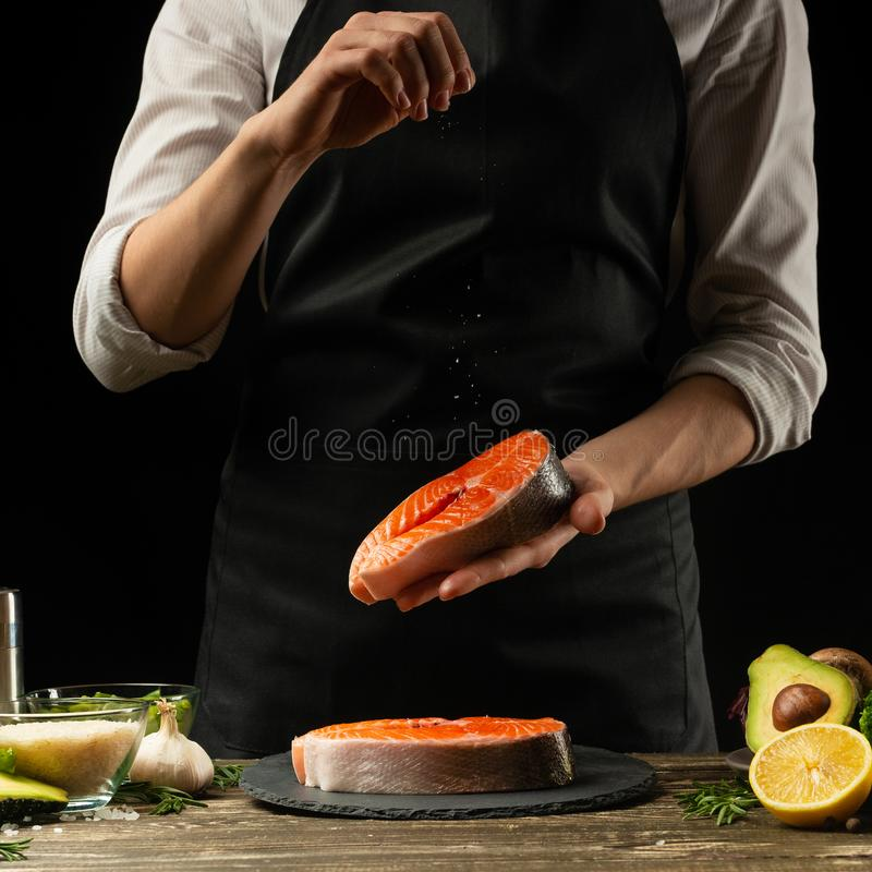 The chef prepares fresh salmon fish, Crumbu trout, sprinkles sea salt with ingredients. Preparing fish food. Salmon steak. Cooking stock photos