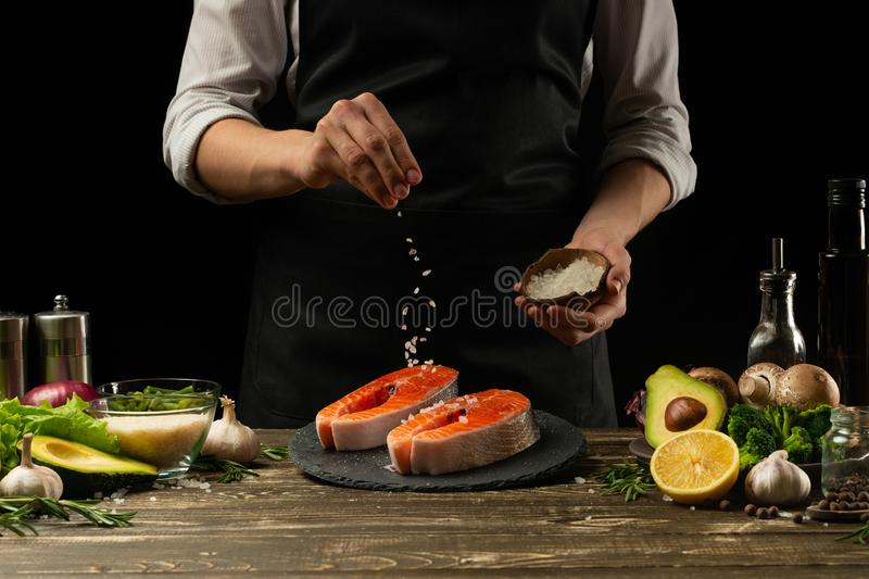 The chef prepares fresh salmon fish, smorgu trout, sprinkling salt with the ingredients. Frost freezing in the air. Preparing to. Cook fish food. Salmon steak stock photography