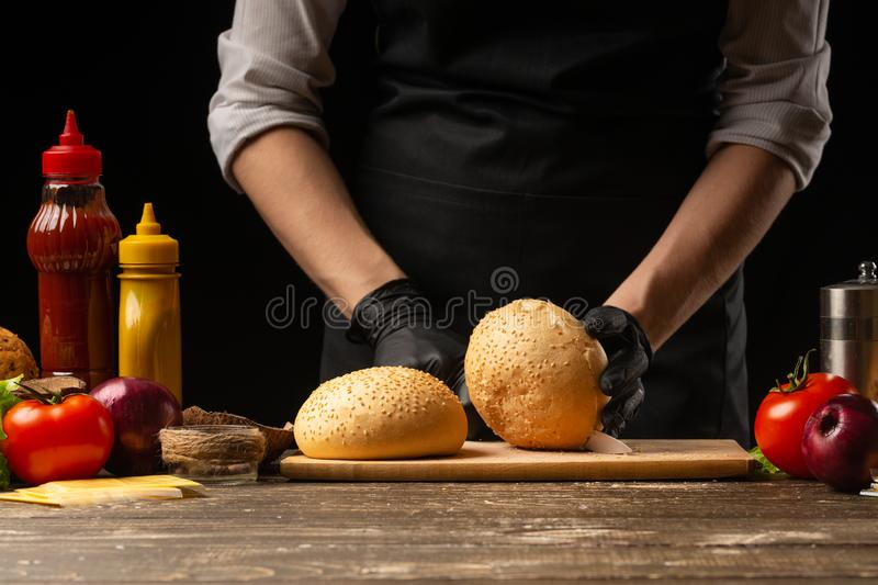 Chef prepares fresh sesame buns for burger cooking, with ingredients on the background, restaurant business, fast food, tasty food royalty free stock photography