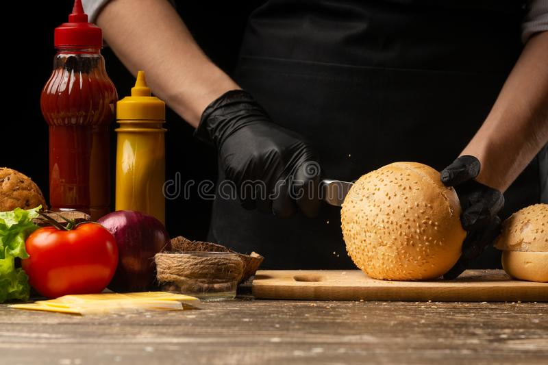 Chef prepares fresh sesame buns for burger cooking, with ingredients on the background, restaurant business, fast food, tasty food. Gastronomy, cooking, menu royalty free stock photography