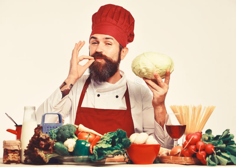 Chef prepares meal showing Perfect sign. Cook with happy face. In uniform sits by table with vegetables and kitchenware. Restaurant cuisine concept. Man with stock photo