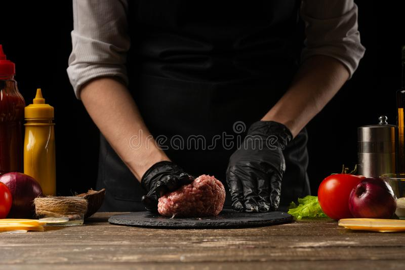 Chef prepares a meat patty with minced meat for a burger. Delicious and unhealthy food. Horizontal photo, Taste food concept.  royalty free stock photos
