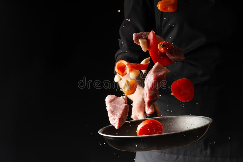 Chef prepares meat with vegetables, on a black background, roasting, tasty food, recipe book, menu, restaurant business royalty free stock images