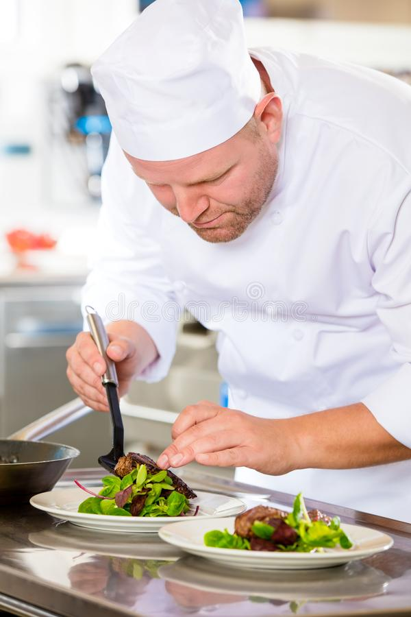 Chef prepares steak dish at gourmet restaurant royalty free stock photos