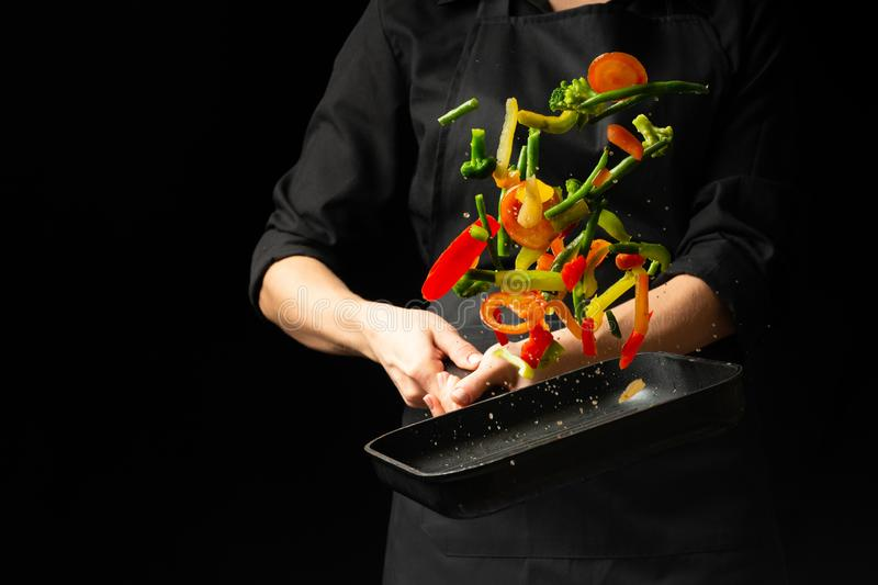 The chef prepares the vegetables on the pan. Black background for copying text. Restaurant business and advertising royalty free stock photography