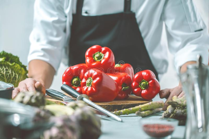 Chef prepares vegetables to cook in the restaurant kitchen royalty free stock images