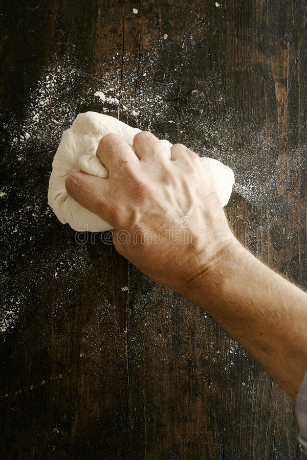 Chef preparing dough kneading it with his hand. Chef preparing pizza dough kneading it with his hand on a floured kitchen counter, overhead close up view royalty free stock image