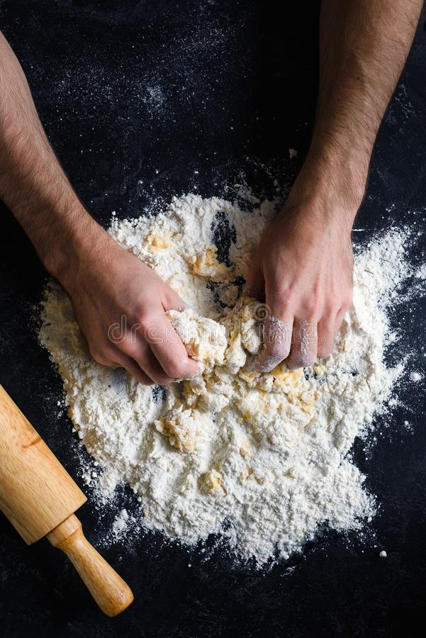 Chef preparing dough for pasta. Hands kneading dough. Chef making pasta dough. Man hands kneading dough on dark background, top view. Bakery, pastry preparations royalty free stock photos