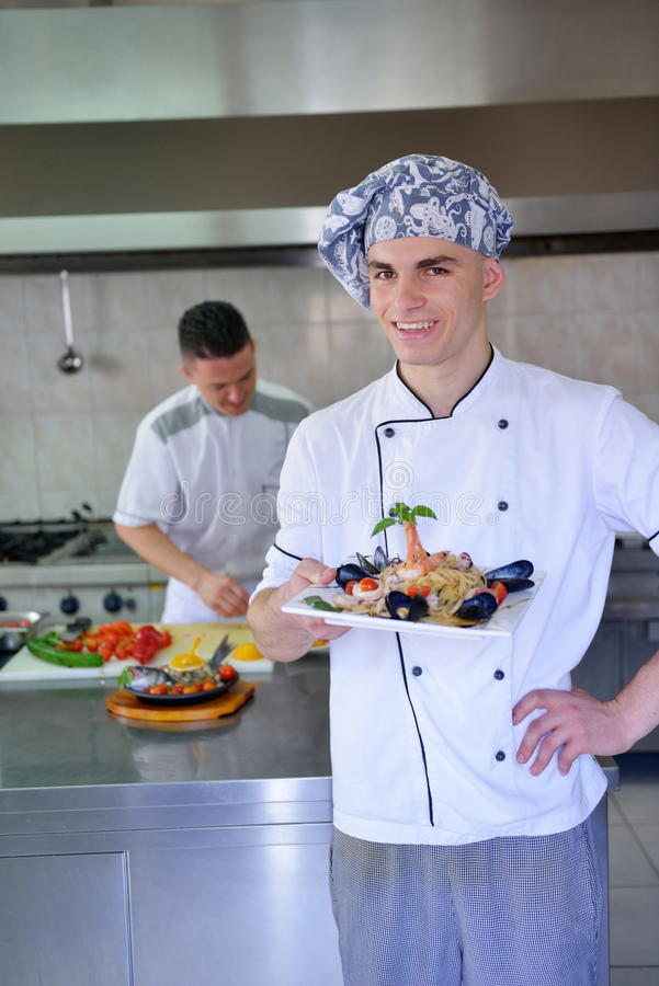 Chef preparing food. Handsome chef dressed in white uniform decorating pasta salad and seafood fish in modern kitchen royalty free stock photos