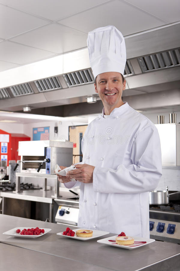 Chef preparing gourmet desserts in commercial kitchen royalty free stock photography