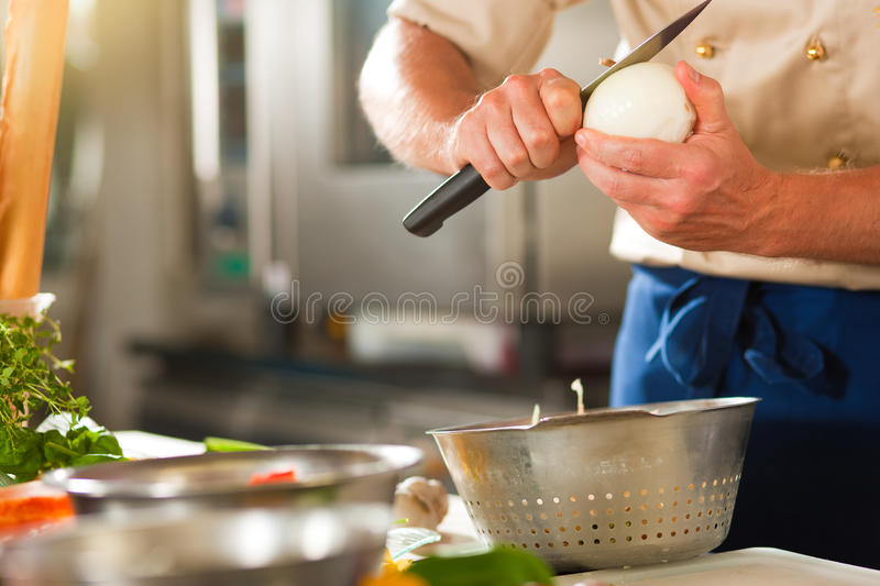 Chef preparing onion in restaurant or hotel kitchen. Close up of chef in a commercial restaurant or hotel kitchen working, he is preparing an onion and royalty free stock photo