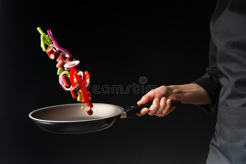 Chef preparing pepperoni sausages with green beans, sweet bell peppers and red onion rings, on a black background, close-up royalty free stock image