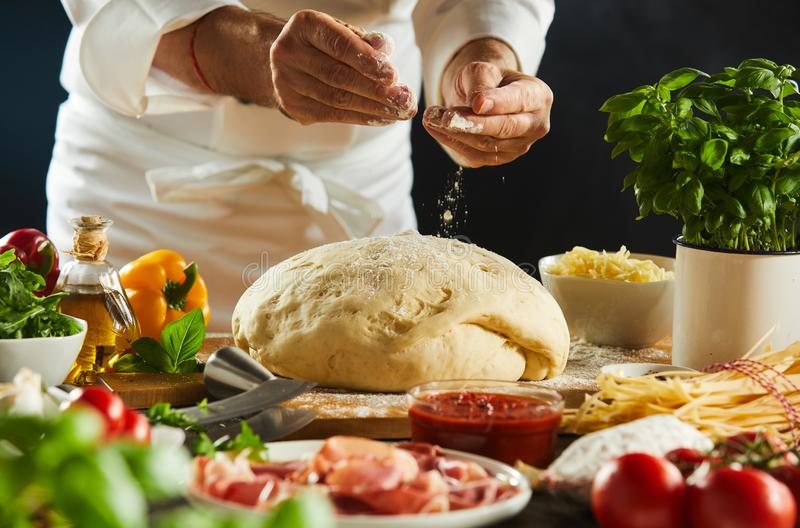 Chef preparing pizza dough in a restaurant royalty free stock photos