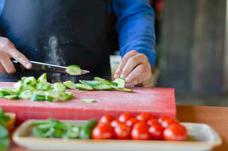 Chef is preparing Turkish breakfast on the wooden table. Turkish breakfast preparation. Chef is cutting cucumber for breakfast stock photography