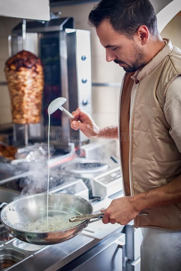 Chef preparing tzatziki sauce for gyros. Traditional greek fast food stock photography