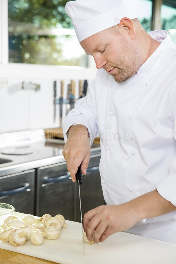 Chef professionnel préparant des légumes à un plat sain photos libres de droits
