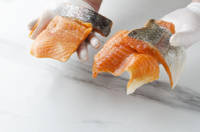 Man holding several pieces of fresh raw salmon.Tasty pieces of fish royalty free stock images