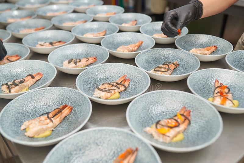 Chef puts shrimp in plates in the kitchen. Chef puts shrimps in many plates in the kitchen in black gloves stock photography