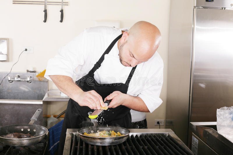 Chef putting grated parmesan to an italian pasta royalty free stock images