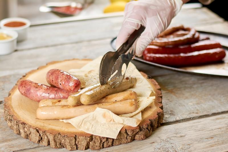 Chef putting grilled sausages on platter. Cook hand with kitchen stainless steel tongs putting roasted sausages on wood. Delicious restaurant food stock photo