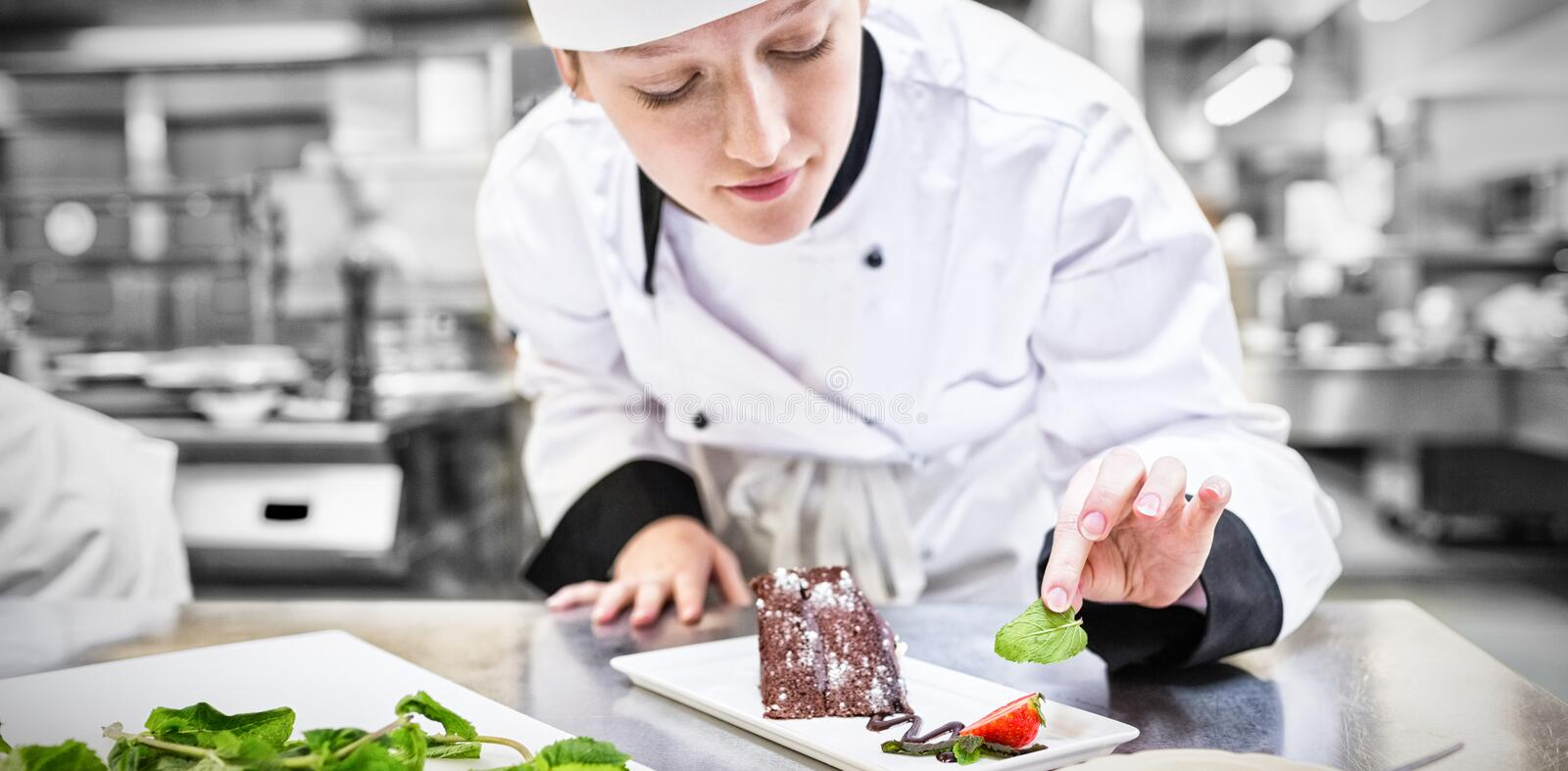 Chef putting mint with her chocolate cake royalty free stock photography