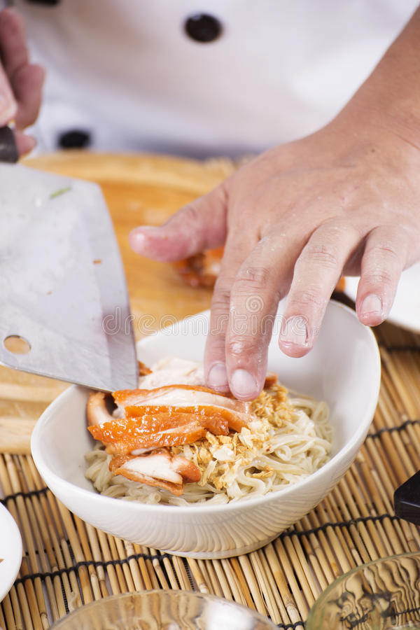 Chef putting roast chicken to bowl of Noodle. / Cooking Noodle concept royalty free stock photography