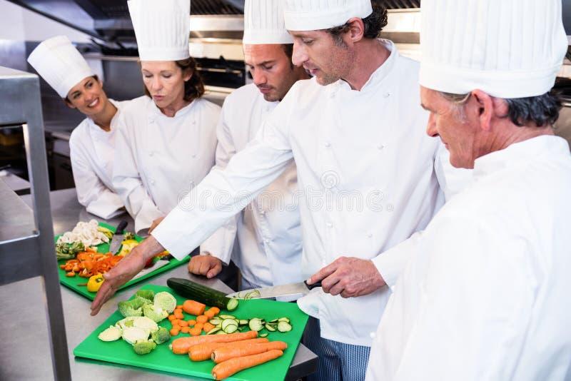 Chef que enseña sus colegas a cómo cortar verduras foto de archivo