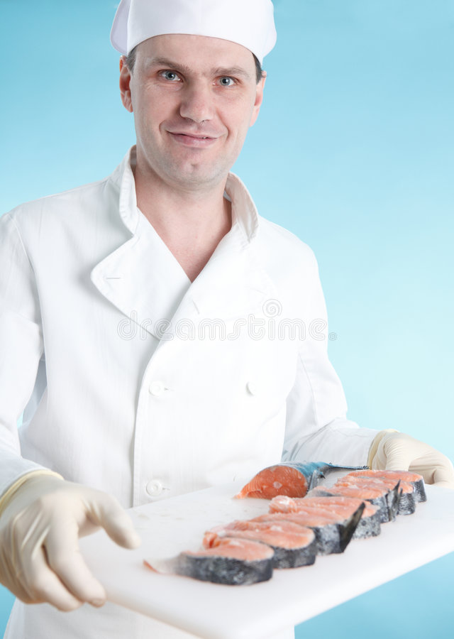 Chef with raw fish on cutting board royalty free stock image