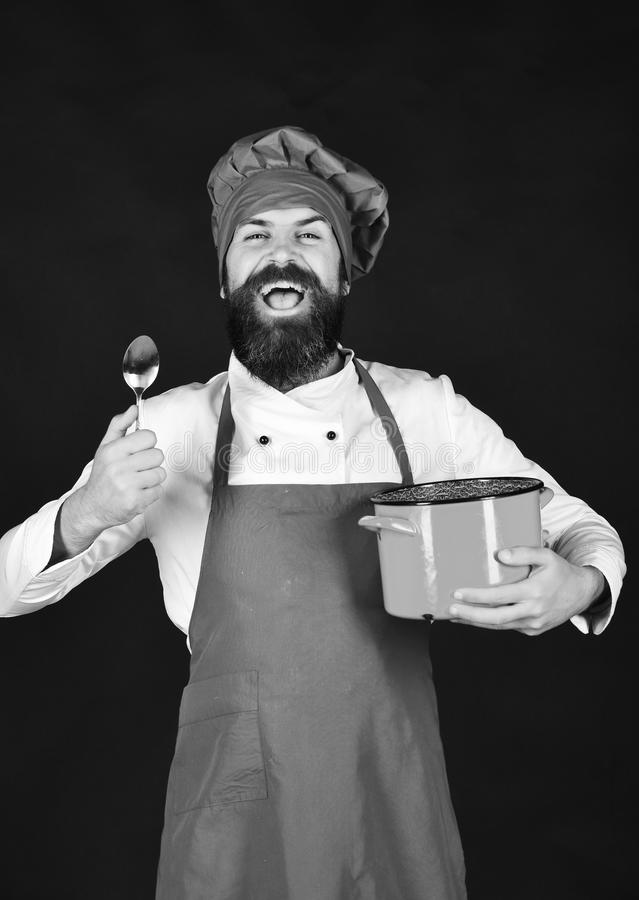 Chef with red casserole or saucepan and cutlery. Cook with happy face in burgundy hat and apron holds soup pot and spoon. Man with beard holds kitchenware on stock images