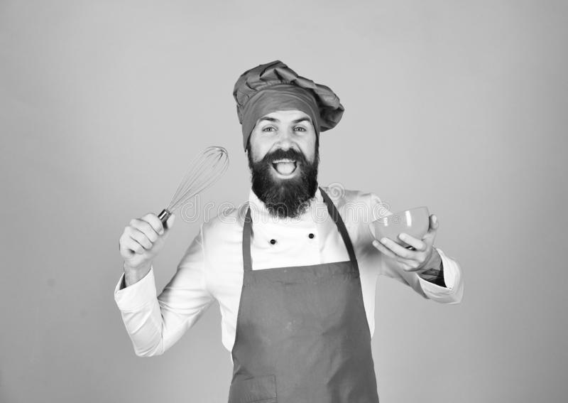 Chef with plate and whipping utensil. Cook with cheerful face royalty free stock image