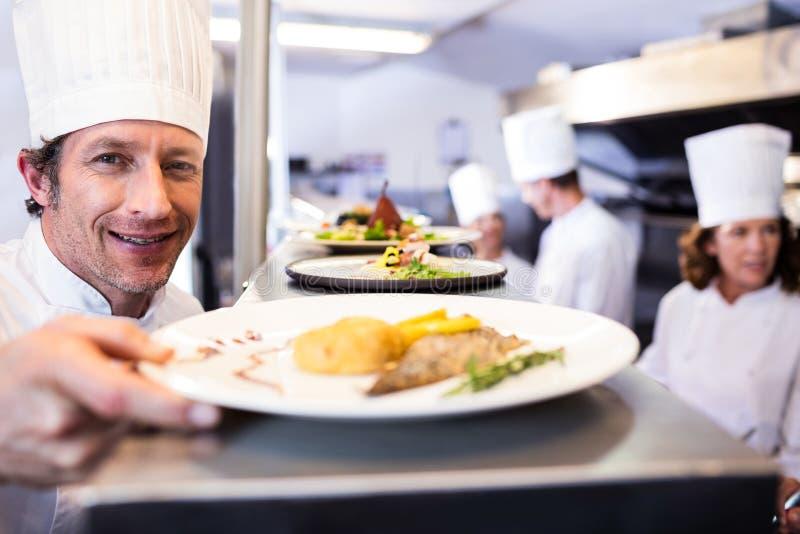Chef remettant des plats de dîner par la station d'ordre photo stock