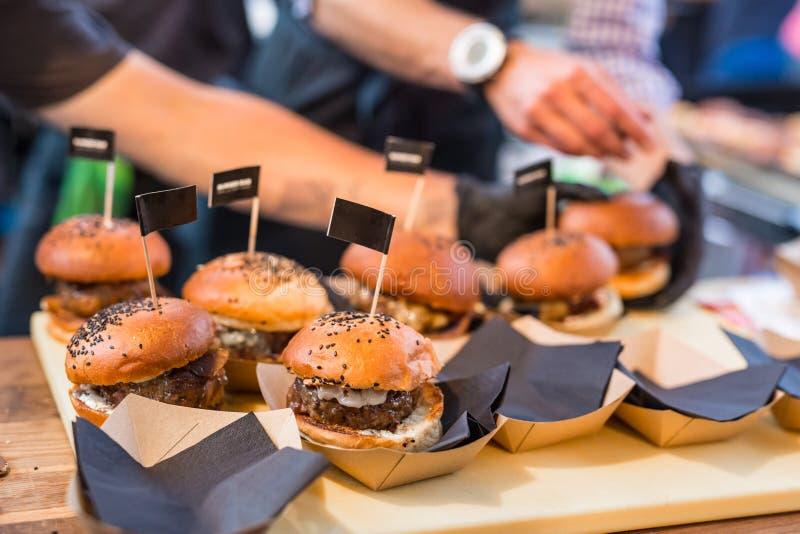 Chef rendant des hamburgers de boeuf extérieurs sur l'événement international de festival de nourriture de cuisine ouverte photographie stock