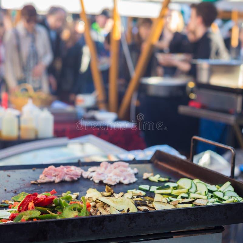 Chef rendant le poulet avec l'enveloppe végétale grillée de tortilla extérieur sur la stalle de rue images libres de droits