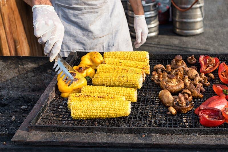 Chef rendant les légumes grillés extérieurs sur l'événement international de festival de nourriture de rue de cuisine ouverte photographie stock
