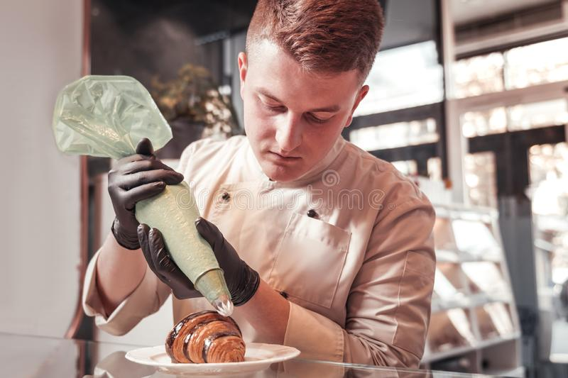 Chef of the restaurant decorating the croissant with cream royalty free stock photos