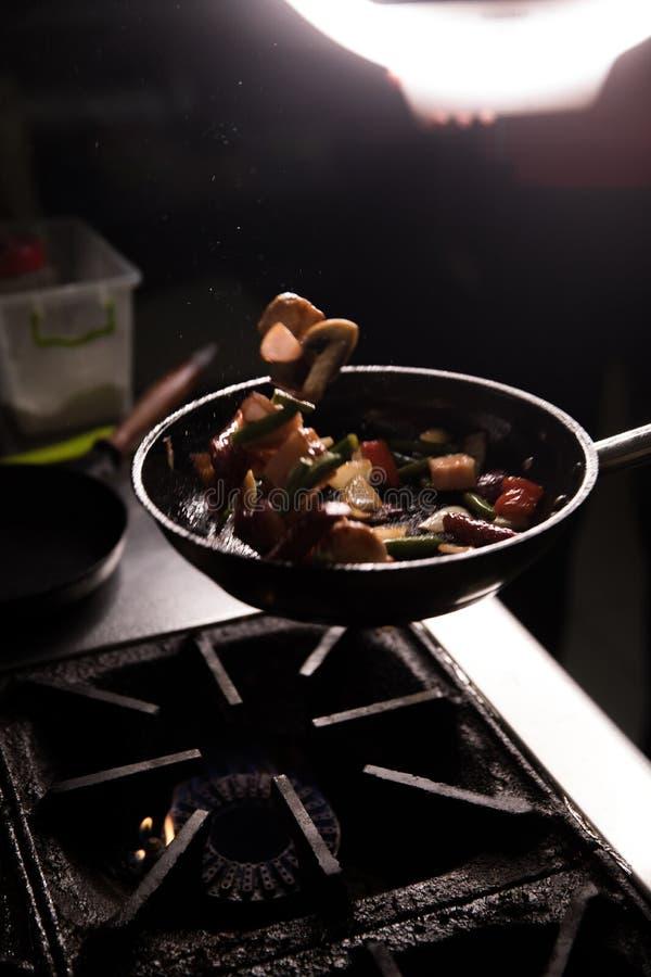 Chef In Restaurant Kitchen préparant le fond d'obscurité de nourriture photos stock