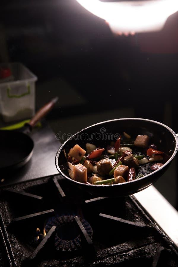 Chef In Restaurant Kitchen préparant le fond d'obscurité de nourriture photo libre de droits